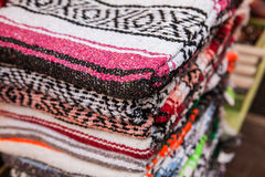 Colorful Mexican serapes hang in row. Mexican serape fabric colorful pattern texture background Royalty Free Stock Photography
