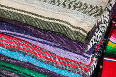 Colorful Mexican serapes hang in row. Stock Images