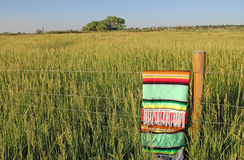 Colorful Mexican Zarape Blanket Placed on a Fence. Colorful zarape, Mexican blanket, placed on a barbed wire fence that separates a road and a large wheat field Stock Photos