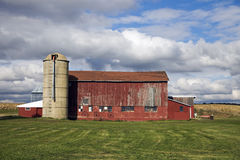 Colorful Midwest scene. Red barn under cloudy sky stock photo