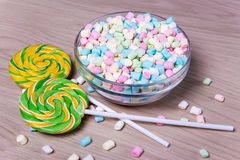 Colorful mini marshmallows and lollipops on wooden table Royalty Free Stock Photo