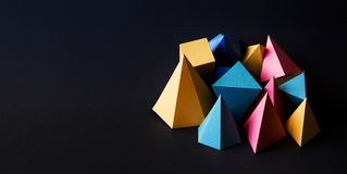Colorful minimalistic composition abstract geometric solid figures on black textured paper background. Pyramid prism. Rectangular cube yellow blue pink green royalty free stock photography