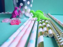 Colorful mint, pink and golden drinking straws for beverages with dinosaur toys. Party theme composition. Colorful mint, pink and golden drinking straws for royalty free stock photos