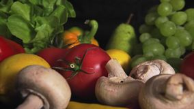 Colorful mix of fruits and vegetables. Black background stock footage