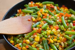 Colorful mix of vegetables is fried in a frying pan close up. Food stock photography