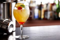 Colorful mixed drink. Cool, colorful summer drink with orange, lime and cherry, shot in bar with shaker royalty free stock photography
