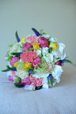 Colorful mixed wedding bouquet positioned on a white cushion. Vertical shoot of a colorful summer wedding bouquet with roses, peonies and greenery. Ready detail Royalty Free Stock Image