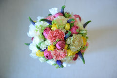 Colorful mixed wedding bouquet positioned on a white cushion viewed from above. Beautiful summer flower arrangement for the bride-to-be with peonies, yellow royalty free stock photography