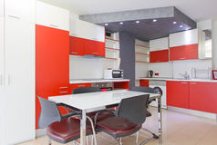 Colorful modern kitchen. Colorful spacious modern kitchen interior decor with orange cabinets, table and chairs Royalty Free Stock Photos