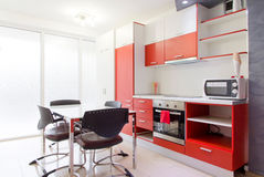 Colorful modern kitchen. Colorful spacious modern kitchen interior decor with orange cabinets, table and chairs Royalty Free Stock Images