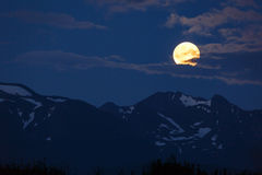 Colorful moonrise over snowy mountain peaks Stock Photo