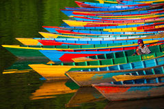 Colorful moorage. POKHARA, NEPAL - APRIL 13, 2012: Colorful moorage. Bright and colorful boats standing in one row on the water. A boatman young Nepali boy is Royalty Free Stock Photos