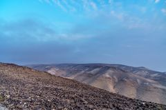 Colorful morning landscape of magic sunrise in judean desert in Israel. Outdoor nature with nobody on photo. Deep blue sky and clouds, mountains and rocks Stock Photos
