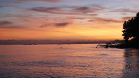 Colorful morning sky reflects to an open sea. Colorful morning sky reflects to an open sea with a small traditional boat on the mangrove shore royalty free stock images