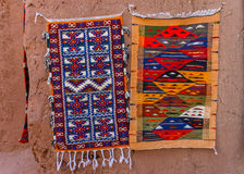 Colorful Moroccan Berber carpets hanging on adobe wall Royalty Free Stock Images
