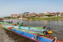 Boats on Nam Song River in Vang Vieng, Laos. Colorful motoboats and few people on the Nam Song River and hotels in Vang Vieng, Vientiane Province, Laos, on a royalty free stock images