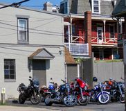 Colorful motorcycles parked in front of gray building. stock photo