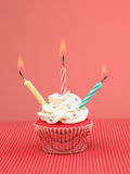 Colorful muffin candles. Muffin on red table with three lit candles on pink background Stock Photos