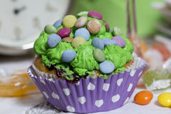 Colorful muffin. With cream and candies on the table Royalty Free Stock Photos