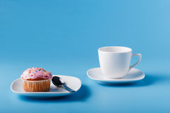 Colorful muffin on saucer. Blue background Stock Photo