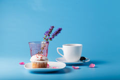 Colorful muffin on saucer with flower petal Royalty Free Stock Images
