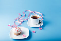 Colorful muffin on saucer with flower petal and ribbon Stock Image