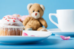 Colorful muffin on saucer with flower petal and toy Stock Photo