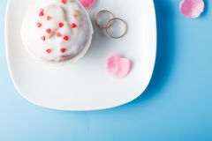 Colorful muffin on saucer with wedding rings Royalty Free Stock Photo