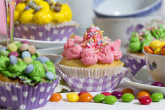 Colorful muffins. Crazy colorful muffins and candies with tea cups on a table Stock Photography