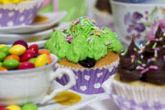 Colorful muffins. A table full of colorful muffins and a cup of tea ful of colorful candies Royalty Free Stock Images
