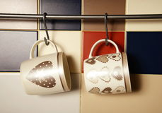 Colorful mugs on hooks Stock Photos
