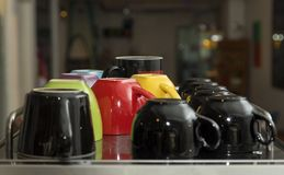 Colorful mugs in a row in a coffee shop or kitchen royalty free stock images