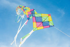 Colorful multi-color kites flying in blue sky Stock Images