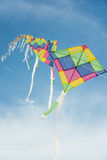 Colorful multi-color kites flying in blue sky Stock Photos