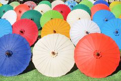 Colorful multicolored paper umbrella group on grass floor, decoration for background stock images