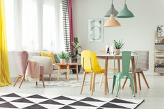 Colorful multifunctional living room. Pink armchair next to a beige sofa in multifunctional living room interior with colorful chairs at the dining table royalty free stock photography