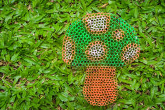 Colorful mushroom on green grass handmade with plastic straw. Stock Image