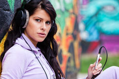 Colorful music. Yong beautiful woman holding her cellphone and listening to music at schoolyard Royalty Free Stock Photography