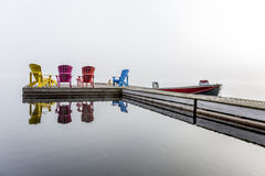 Colorful Muskoka Chairs on a Dock. Colorful Muskoka Chairs Arranged on a Dock with a Small Motorboat on a Misty Morning - Haliburton, Ontario, Canada stock image