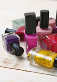 Colorful nail polish bottles on light wooden background Royalty Free Stock Images