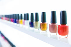 Colorful nail polish colors in a row at nails saloon on white Stock Photos