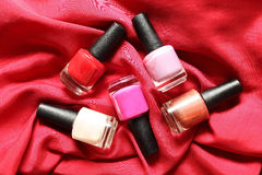 Colorful nail polish on red background Stock Photography