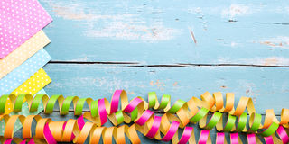 Colorful napkins and streamers on wooden table with copyspace. Concept festivity decoration royalty free stock photography