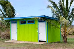 Colorful neat clean green public restroom facility. Flanked by tropical palm trees in a park on Oahu, Hawaii with signs and doors for men and women Royalty Free Stock Images