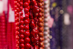 Colorful necklaces. Different colored necklaces hanging on stall with bright red ones in foreground Royalty Free Stock Image