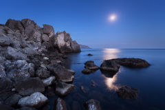 Colorful night landscape with full moon, lunar path and rocks in summer. Mountain landscape at the sea. Stock Photo