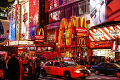 Colorful Night Life Times Square New York City. Traffic speeds past as pedistrians waits under the colorful billboards and bright lights of the Times Square area royalty free stock image