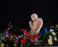 Colorful Night time scene Angel praying atop a tomb royalty free stock images