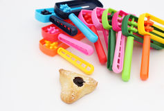 Colorful noisemakers and one Haman ear cookie. Colorful noisemakers for kids to make noise once the name of Haman is read from the Megila. A Jewish tradition on stock photography