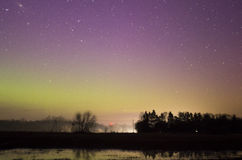 Colorful Norther Lights over Distant Highway. Powerful northern lights over night sky over distant highway. You can see the glow of the headlights on the road Royalty Free Stock Photos